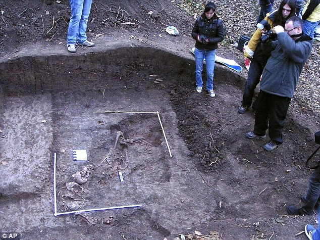 Forensic experts take pictures of human remains in a forest near Poprican, northern Romania. A mass grave containing the bodies of an estimated 100 Jews killed by Romanian troops has been discovered