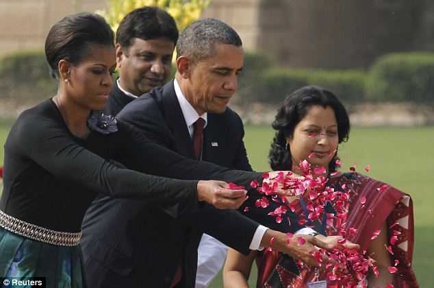 The First Lady wore her hair up and recycled the belt she wore on Saturday as she tossed flowers at the Gandhi memorial