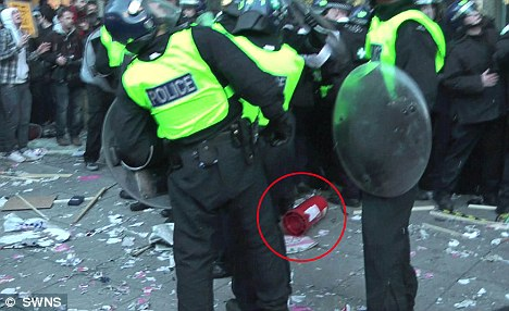 Near miss: The fire extinguisher lands near riot officers