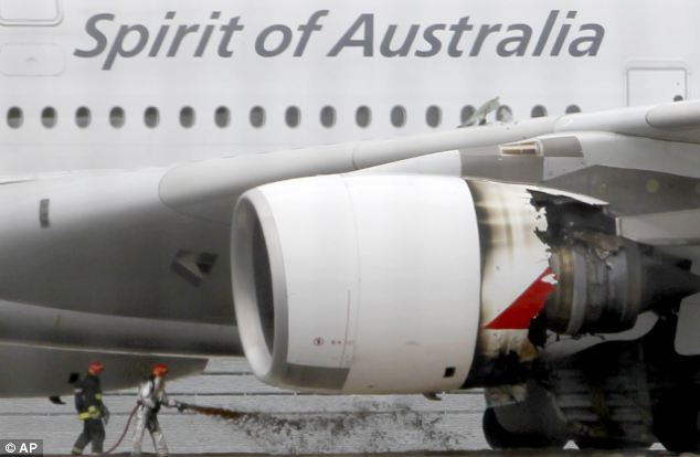 Firefighters surround a Qantas jetliner which made an emergency landing at Singapore's Changi International Airport