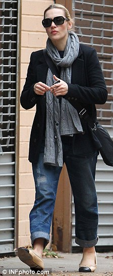 Wrapped up warm: Winslet went for a winter chic outfit in a black coat and long grey scarf with jeans and pumps
