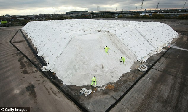 Preparing for the freeze: Workers shovel road salt at the London Strategic Salt Reserve yesterday