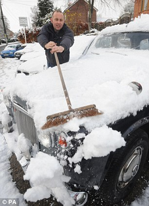 David Mathewson clears snow from a vintage car on his garage forecourt in Thornton-le-Dale, North Yorkshire