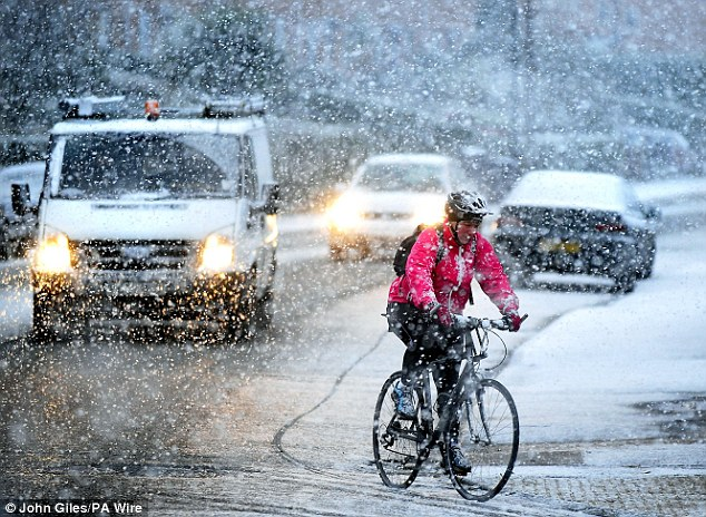 Cold journey: A cyclist makes their way through the snow in York yesterday afternoon