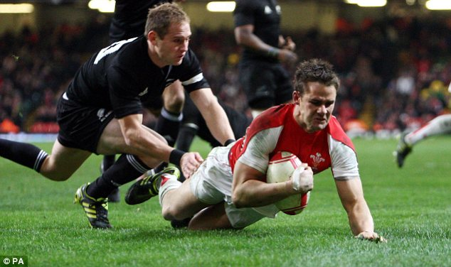 On the slide: Wales's Lee Byrne crosses for a consolation score