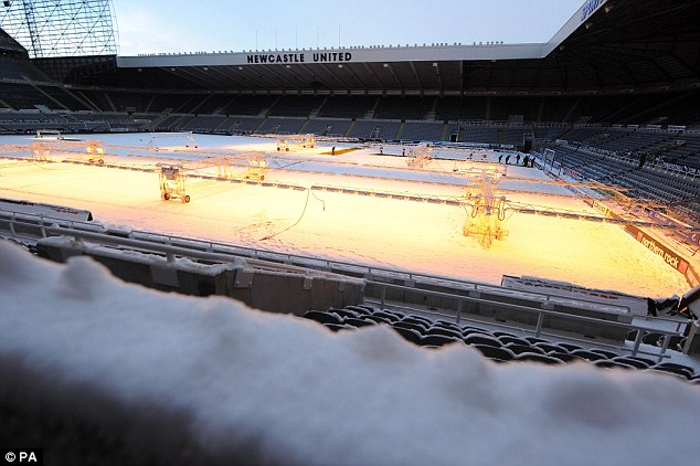 Struggle: Newcastle United ground staff attempt to clear the pitch  before tomorrow's match against Chelsea