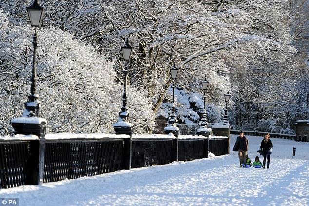 Landscape transformed: Walkers enjoy the snow today in Jesmond Dene, Newcastle