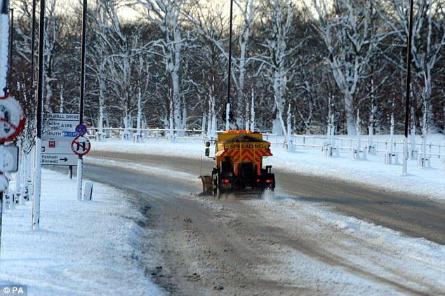 At work: A gritter in Newcastle city centre today spreads salt and ploughs the roads