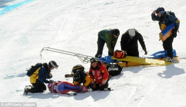 Help arrives: Rescue workers tend to Alcott after her crash. She was airlifted to a hospital in Banff