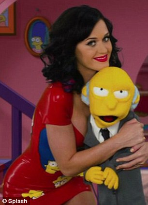 Festive hug: Racy Katy Perry gave Mr Burns a raunchy hug while wearing her PVC red dress and scarlet lipstick