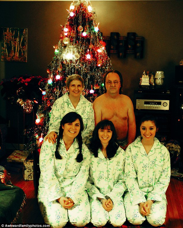 Forgotten something?: A family poses in front of their Christmas tree. But where has dad's pyjama top gone?