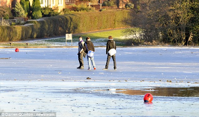 Dicing with danger: Three teenagers walk across a frozen lake in Bournville, Birmingham