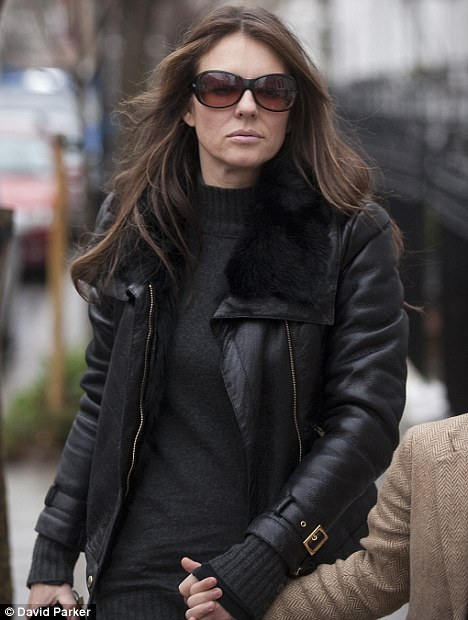 Glum: Liz Hurley looked pale and drawn today as she walked with son Damian near her home in Chelsea, west London - the first time she's been seen in public since news of the split with husband Arun Nayar and affair with Shane Warne emerged