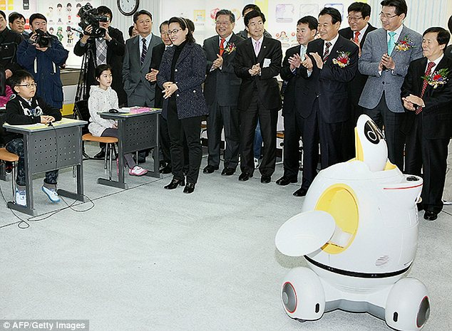 Educational officials in Daegu applaud the robot teacher, which can move its arms and wheel around the floor