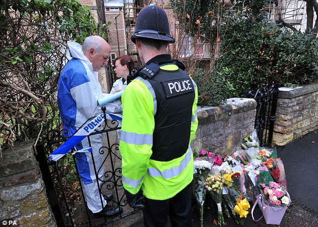 Search: A police officer guarding the block of flats in Clifton, Bristol, where Jo lived below her landlord Chris Jefferies liaises with the forensics team