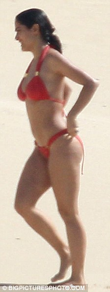 Future's bright: Salma was wearing a bright orange bikini yesterday on her extended holiday on the Caribbean island