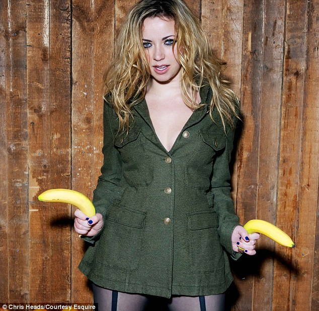 Shoot 'em up: Charlotte messes around on the photoshoot set as she poses in a military-style coat and suspender patterned tights