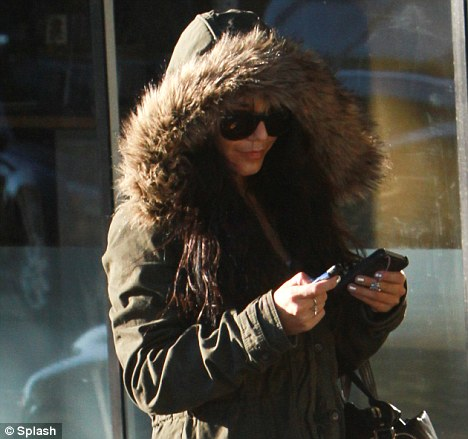 Under wraps: Vanessa Hudgens hides behind a big fur hood as she leaves a chiropractor in Los Angeles yesterday