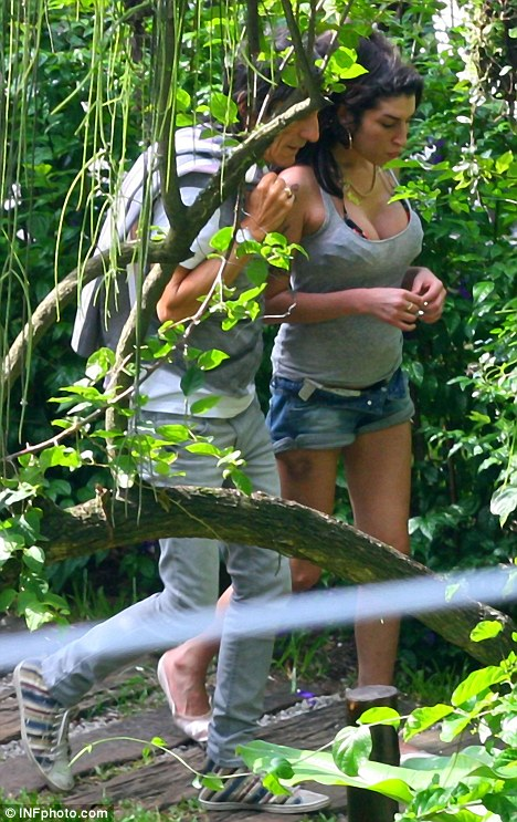 Plenty to talk about: Wood and Winehouse looked deep in conversation as they strolled through the tropical gardens