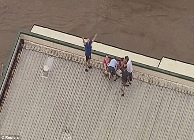 People in Grantham wait to be rescued as the flood water begins to engulf their house