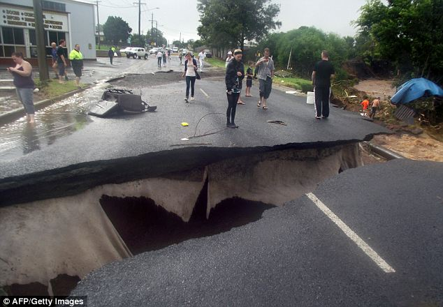 A road destroyed by floods in Toowoomba. Nine people are dead and 66 are still missing after flash floods swept the hill region in eastern Australia