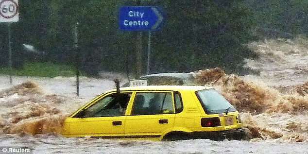 Plea: A passenger waves for help as a car stranded by Toowoomba's flash floods is swamped by the waters at a road junction in the city