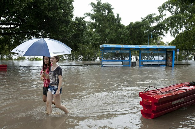 Two girls brave the wet conditions on the flooded Riverside Drive in Brisbane