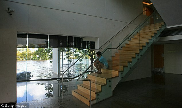 Rising tide: From the safety of his stairs a resident watches the flood level get ever higher outside
