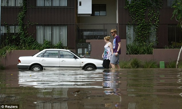 Just beginning: A couple walks past a flooded apartment building in West End with waters expected to rise higher in the next two days