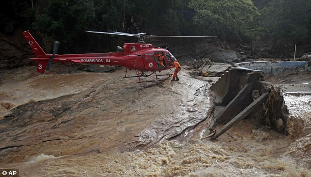 Grounded: Rescue workers were forced to return to their helicopter as the rains came down again, making it hard to search for mudslide victims