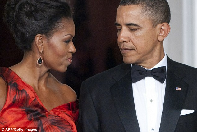 Looking good: Mrs Obama appears to be suppressing a smile at her husband as the pair wait to greet Mr Hu