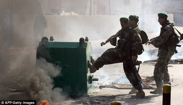 Out of control: Lebanese soldiers disperse burning articles set alight by in Beirut