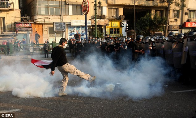 Tear gas: A young man kicks back a canister which has been hurled by a riot policeman