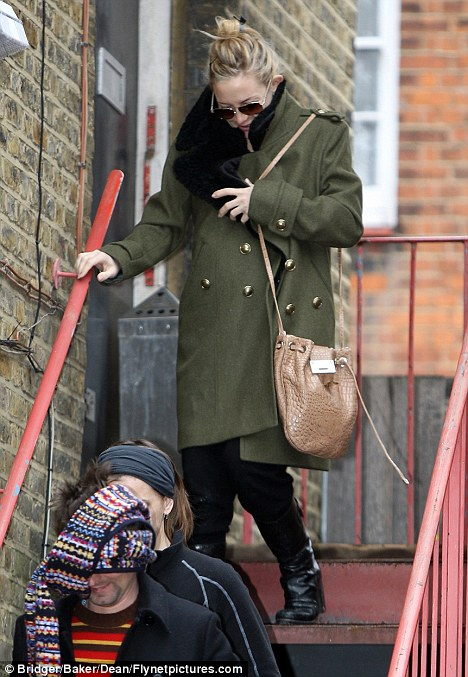 Fooling no one: Kate Hudson keeps her baby bump out of sight in a Burberry coat while rock star boyfriend Matt Bellamy tries to hide his face with his scarf