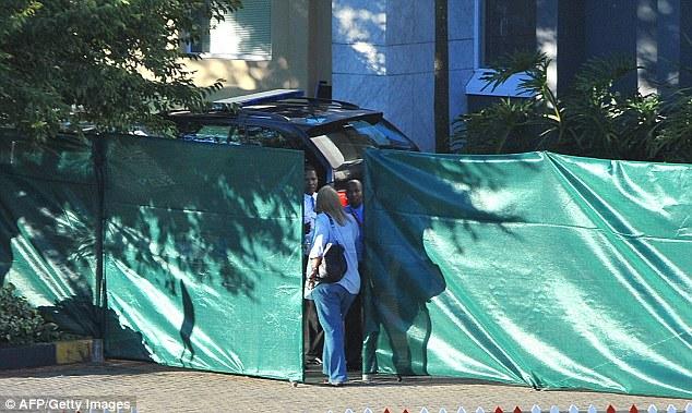 Cordoned off: Mr Mandela's personal assistant Zelda la Grange enters a specially screened area of the car park