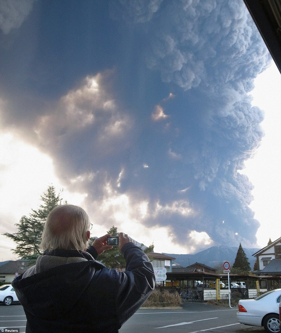Under a cloud: A man takes a picture of erupting Shinmoedake from Takaharu, where an evacuation centre has been established