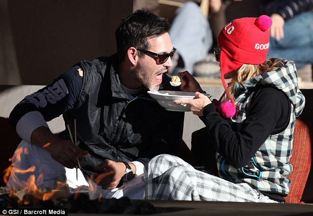 Open wide: LeAnn Rimes feeds Eddie Cibrian mouthfuls of food as they sit beside the fire in Utah
