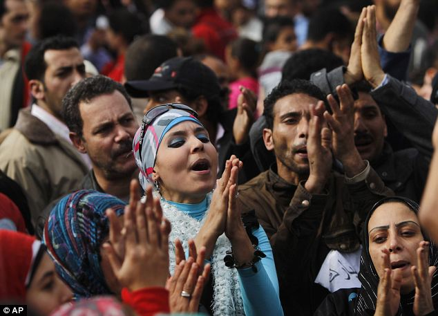 Dash of colour: A brightly dressed woman joins the crowds to pray and chant in Tahrir Square