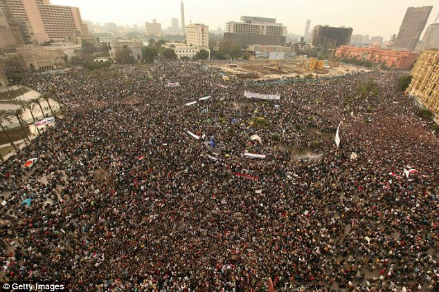 Preparing for long night: Protesters continued to file into Tahrir Square all day with banners, many of them in English, demanding Mubarak's removal