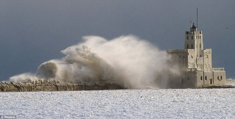 Too fast to freeze: A lighthouse is pounded by waves on Lake Michigan as the storm dumped some 20 inches of snow on Chicago yesterday