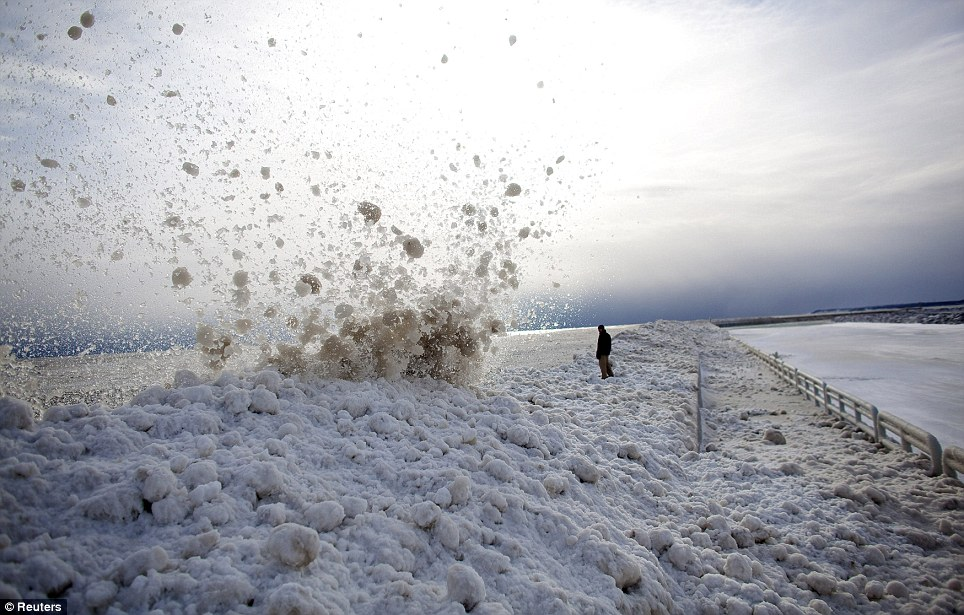Stand back! A man watches as large chunks of ice crash into the break wall at the Milwaukee Marina in Wisconsin after the storm yesterday