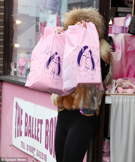 Why do shy? Katie didn't want to be pictured and hid behind two bright pink plastic bags as she left a ballet shop in Surrey