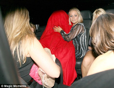 We see you: The reality star came over all camera shy and attempted to hide under a blanket as she left Sugar Hut in Brentwood at 2am
