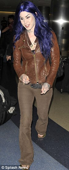 Eclectic: The star of LA Ink teamed a brown leather jacket and jeans with her new bright hair