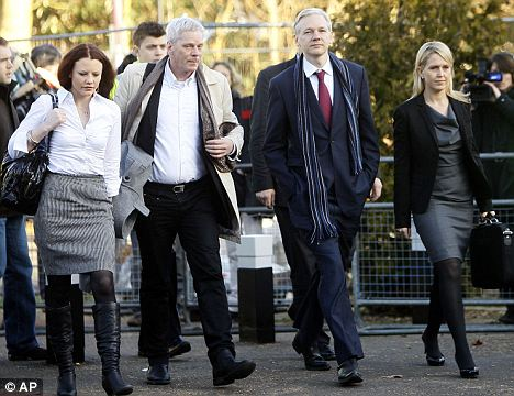 Court case: Assange arrives at Belmarsh Magistrates Court with his legal team earlier this week. He was arrested by British police in November over allegations of rape