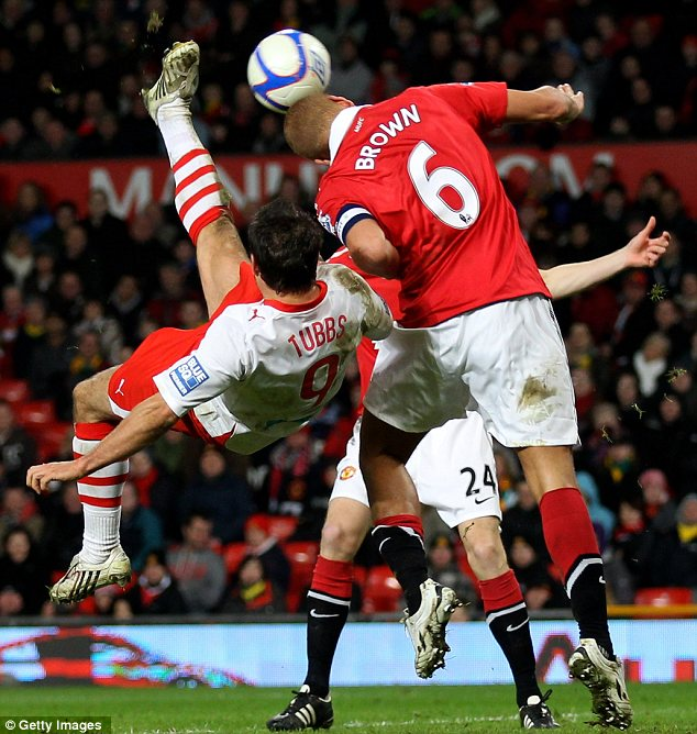 Wes Brown puts his body and head on the line to block an overhead kick from Crawley's Matt Tubbs