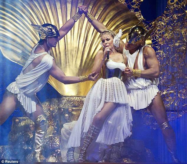 Lean on me: Kylie dances with two muscular male dancers