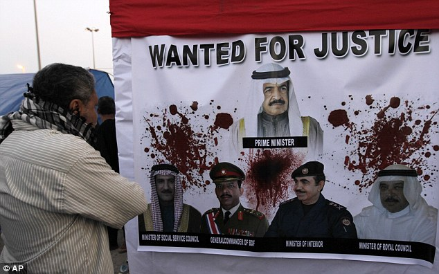Snapshot: A Bahraini anti-government protester looks at a banner at the Pearl roundabout