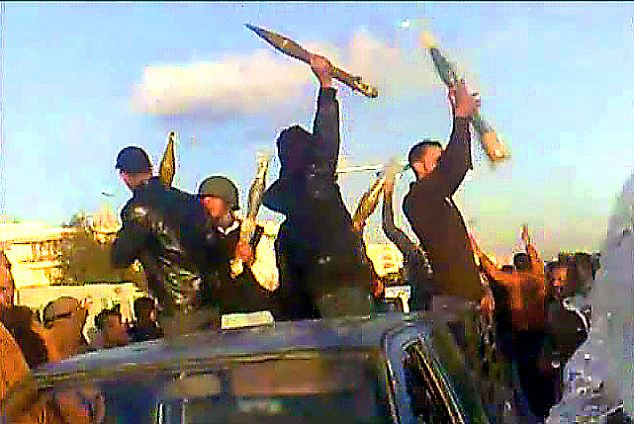 Firepower: Libyan hold aloft guns and rocket grenades believed to have been taken from foreign mercenaries in Benghazi yesterday