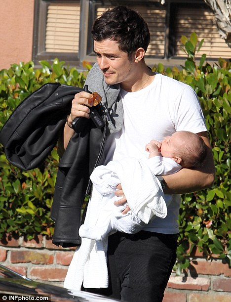 Doting dad: Orlando Bloom carries his seven-week-old son Flynn to the car as he runs errands in Los Angeles